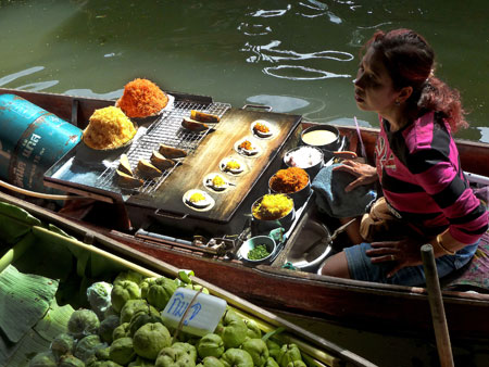 A coconut pancake lady works the floating market in Damnoen Saduak, Thailand.