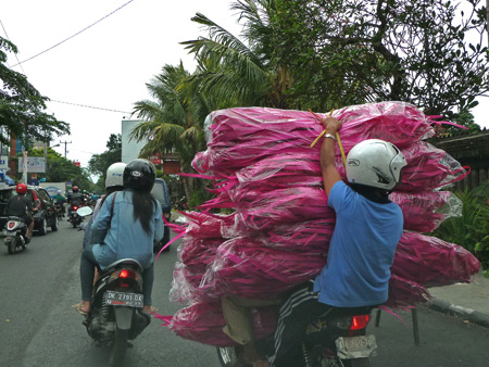 A big delivery makes its way on horseback, I mean motorcycle through Denpasar, Bali, Indonesia.
