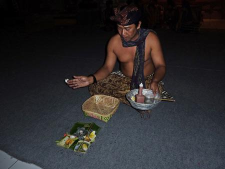 A member of Tetamian blesses the performance space at Pura Agung Peliatan in Peliatan, Bali, Indonesia.