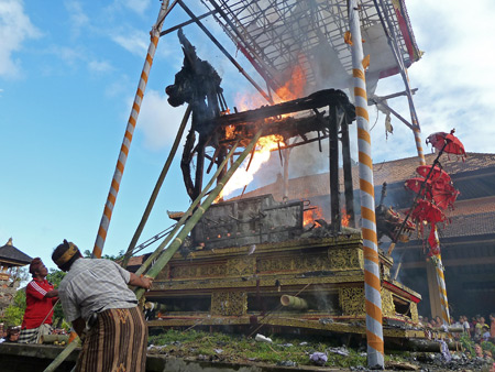 A man aims a flamethrower at the body of Tjokorda Putra Di Armayudha during the royal cremation ceremony at Pura Dalem Puri in Ubud, Bali, Indonesia.