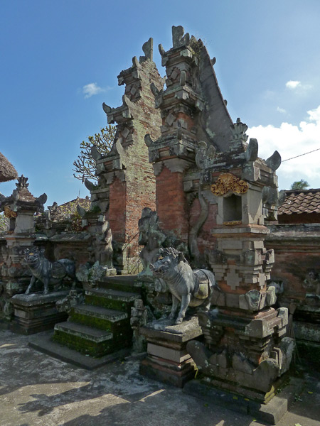 A Balinese Hindu temple gate with guardian boars in Peliatan, Bali, Indonesia.