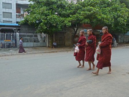 Three Buddhist monks shlep by in front of the Royal Guest House to collect their morning alms in Mandalay, Myanmar.