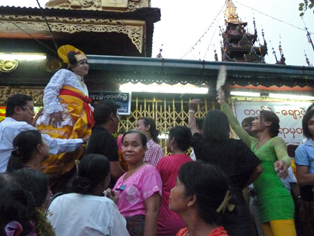A nat kadaw clowns around outside the main Buddhist temple at the Nat Pwe in Taungbyone, Myanmar.