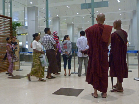 Buddhist monks wait for passengers to arrive at the airport in Yangon, Myanmar.