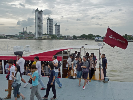 Passengers disembark from a Chao Phraya riverboat at Asiatique mall in Bangkok, Thailand.