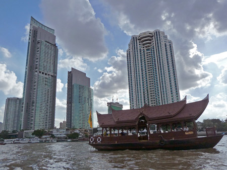 Boat vs. skyscraper on the Chao Phraya river in Bangkok, Thailand.