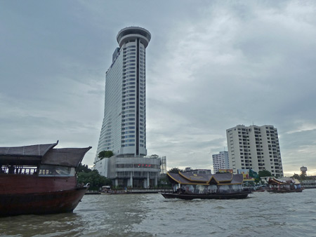 Boats and buildings on the Chao Phraya river in Bangkok, Thailand.