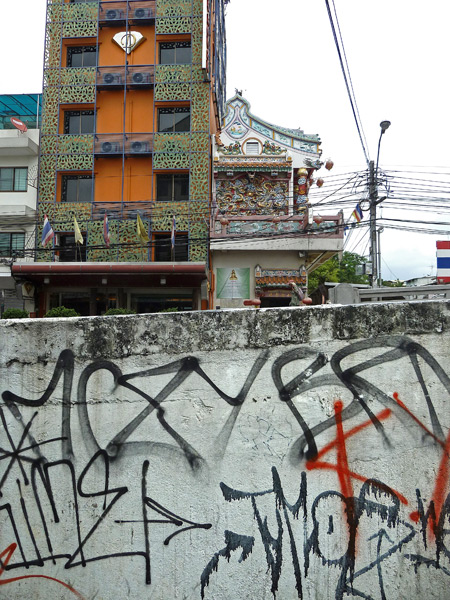 A high-rise, a Chinese Buddhist temple and graffiti peacefully co-exist in Banglamphu, Bangkok, Thailand.