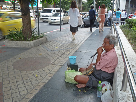 A street musician kicks out the jams on a harmonica and a tambourine backed up with pre-recorded rhythms in Bangkok, Thailand.