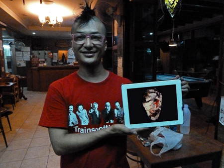 Takuya Ando shows off a This Heat album on his iPad at the Nat 2 Guesthouse in Banglamphu, Bangkok, Thailand.