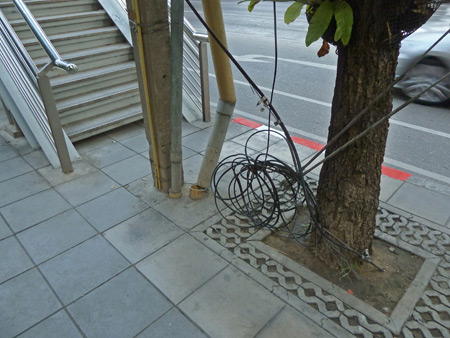A sidewalk quagmire directly in front of a staircase that leads up to the SkyTrain in Bangkok, Thailand.
