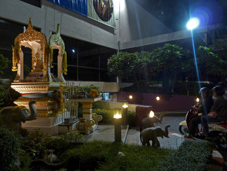 A Thai spirit house in front of a large business near Thanon Sukhumvit in Bangkok, Thailand.
