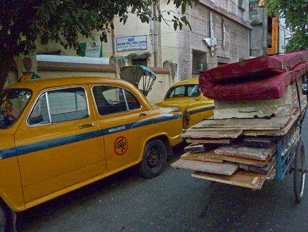 An accidental photo of some taxi cabs and a rickshaw in Kolkata, India.
