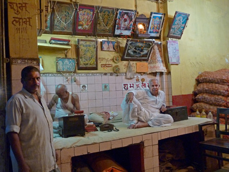 Locals kick back inside a Hindu shrine / potato shack in Kolkata, India.