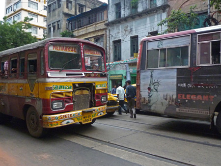 Colorful buses on Bipin Behari Ganguly Street in Kolkata, India.