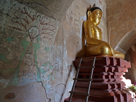 Paintings on stucco walls accompany Buddha inside Dhammayangyi Pahto temple in Bagan, Myanmar.