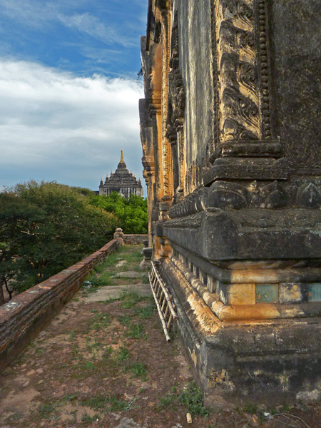 The corner of Shwegugyi Buddhist temple with another temple visible in the distance in Old Bagan, Myanmar.