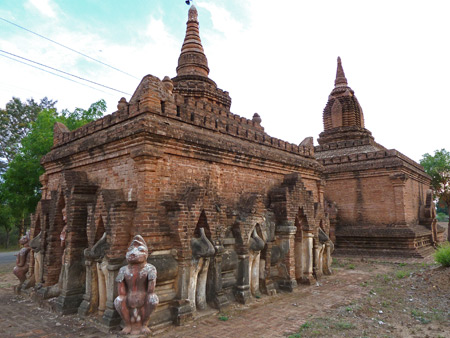 Another Buddhist temple ringed by statues along the road at sunset in Bagan, Myanmar.