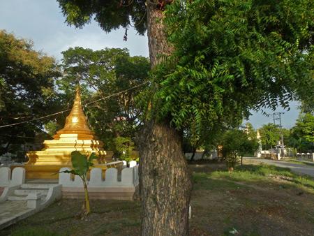 A golden Buddhist pagoda glints in the setting sunlight in Mandalay, Myanmar.