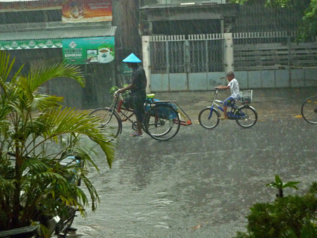 A kid trails a trishaw through the rain in Mandalay, Myanmar.