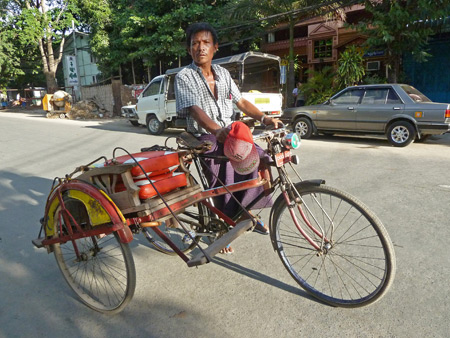 A trishaw driver out in front of the Royal Guest House in Mandalay, Myanmar.