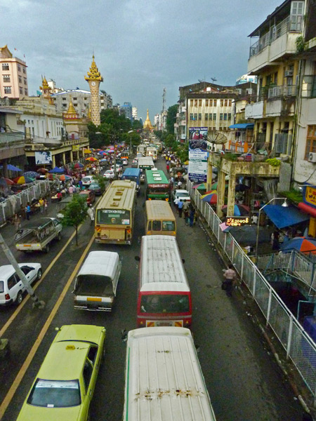 A view from the quad pedestrian bridge of the clocktower and Sule Pagoda in the distance in Yangon, Myanmar.