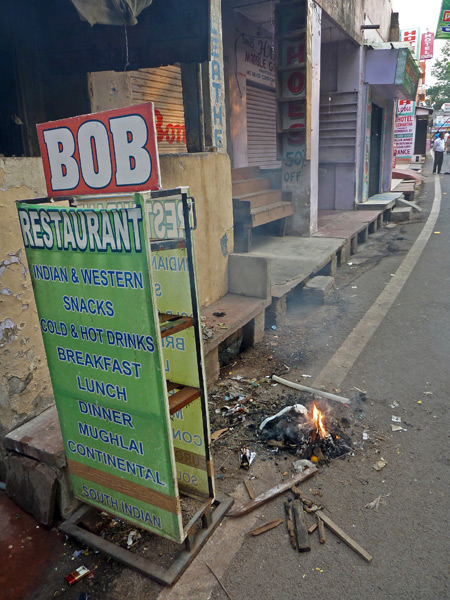 A small fire smoulders in front of Bob Restaurant near the Taj Mahal in Agra, India.