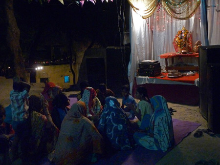 Women sing and play drums at a small Hindu shrine in Agra, India.