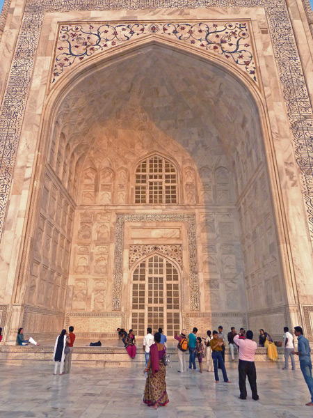 The Taj Mahal's beautiful arches glow in the setting sunlight in Agra, India.