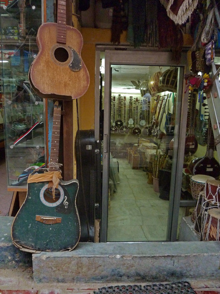A pair of distressed acoustic guitars in a music shop in the Main Bazaar of Paharganj, Delhi, India.