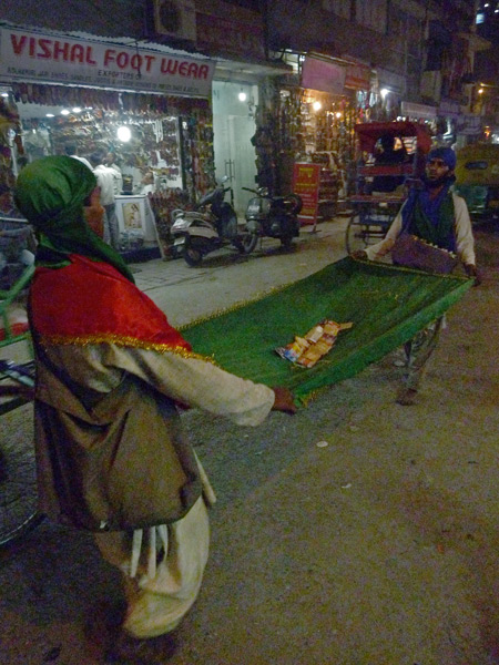 Carriers of the Green Sheet ply the back lanes of the Main Bazaar in Paharganj, Delhi, India.