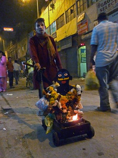 A man wheels a mobile Hindu shrine around the Main Bazaar area of Paharganj, Delhi, India.