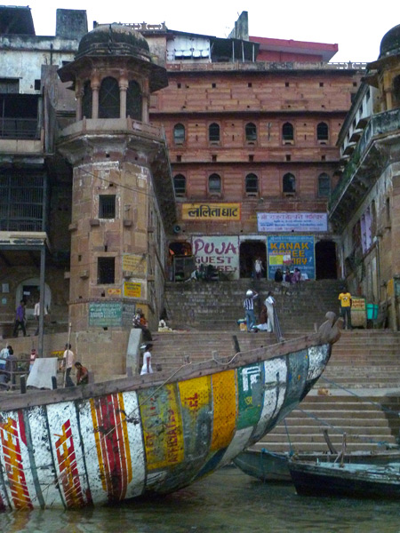 An old boat all patched up with color-splashed signs on the Ganges river in Varanasi, India.