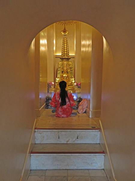 A devotee prays at a Buddha image in the center of the Golden Mount in Phra Nakhon, Bangkok, Thailand.