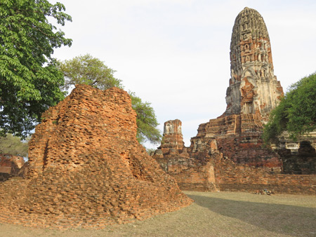 A crumbling chedi and the primary prang at Wat Phra Ram in Ayutthaya, Thailand.
