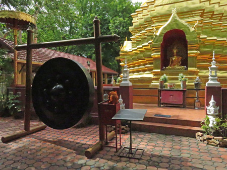 A large gong and a chedi at Wat Sareerikkatart Sirirak in Chiang Mai, Thailand.
