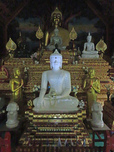 A glowing jade Buddha image at Wat Ou Sai Kham in Chiang Mai, Thailand.