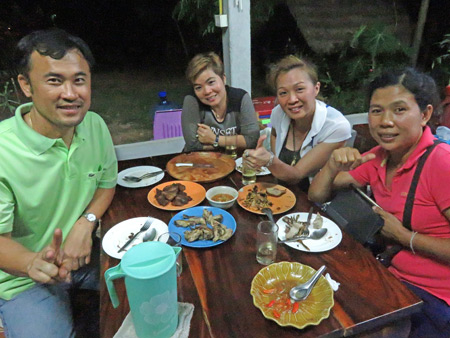 The Mountain Green Resort owner San, Nee, San's wife Jam and Noy enjoy dinner in the cafe in Dan Sai, Thailand.