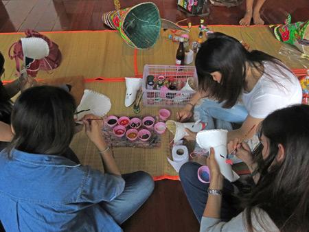 Some girls make Phi Ta Khon masks at the Dan Sai Folk Museum in Dan Sai, Thailand.