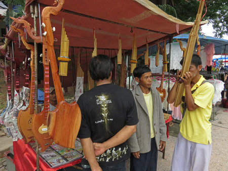 Another man plays the kaen at a market stall selling traditional Thai musical instruments at the Phi Ta Khon festival at Wat Phon Chai in Dan Sai, Thailand.