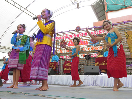 A women's troupe sings and performs a traditional Thai dance at the Phi Ta Khon festival at Wat Phon Chai in Dan Sai, Thailand.