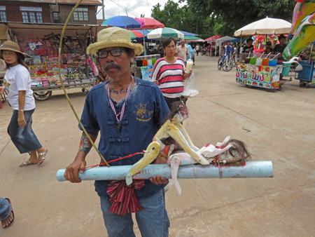 A man performs with an explicit wooden prop at the Phi Ta Khon festival at Wat Phon Chai in Dan Sai, Thailand.