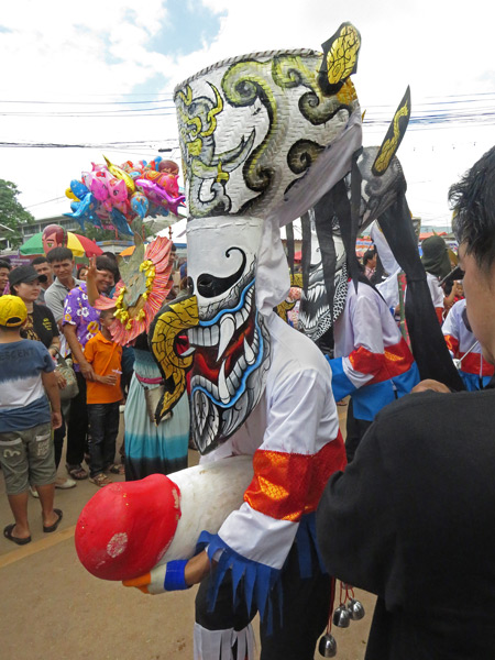 A ghost brandishes a huge phallus in the parade at the Phi Ta Khon festival in Dan Sai, Thailand.