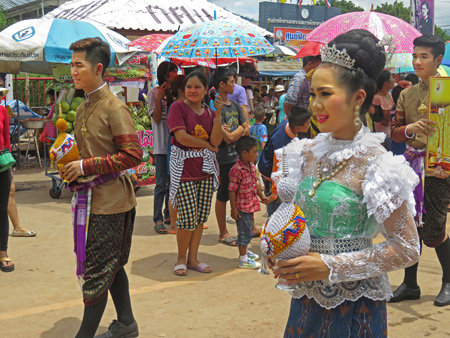 A beauty queen and her king walk in the parade at the Phi Ta Khon festival in Dan Sai, Thailand.