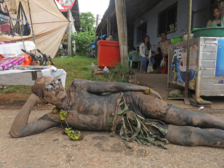 A mud man takes a break after the parade at the Phi Ta Khon festival in Dan Sai, Thailand.