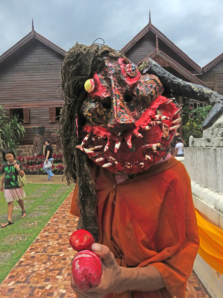 A demon aims his wooden phallus toward me at Wat Phon Chai after the parade at the Phi Ta Khon festival in Dan Sai, Thailand.