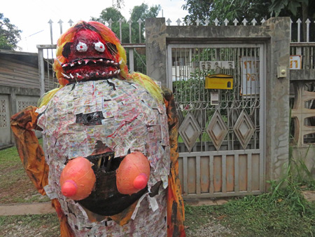 A garish demon propped up on the side of the street after the parade at the Phi Ta Khon festival in Dan Sai, Thailand.