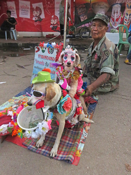 A man and his dogs work the crowd after the parade at the Phi Ta Khon festival in Dan Sai, Thailand.