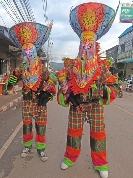 A pair of brightly clad ghosts say goodbye after the parade at the Phi Ta Khon festival in Dan Sai, Thailand.