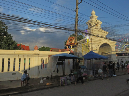 The gate of Wat Pon Chai gets lit up by the setting sun after the parade at the Phi Ta Khon festival in Dan Sai, Thailand.